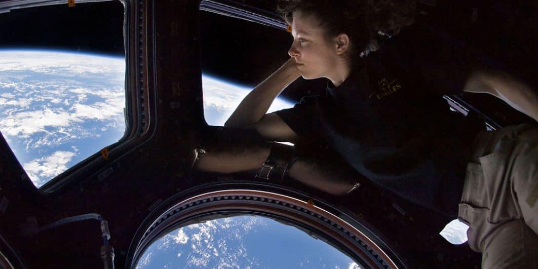 Une femme contemple la Terre vue de l'espace dans l'ISS